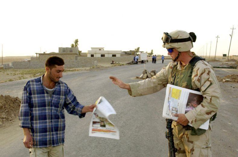 US_Army_soldier_hands_out_a_newspaper_to_a_local_Aug_2004